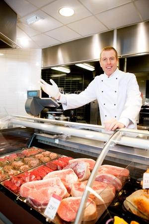 vendedores: Retrato de un carnicero feliz de dar la bienvenida a los clientes de la tienda Foto de archivo