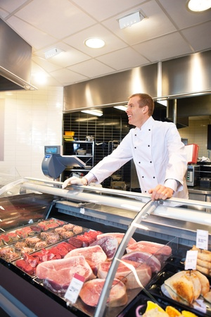 meat counter: Cheerful chef on the counter of frozen meat in the supermarket