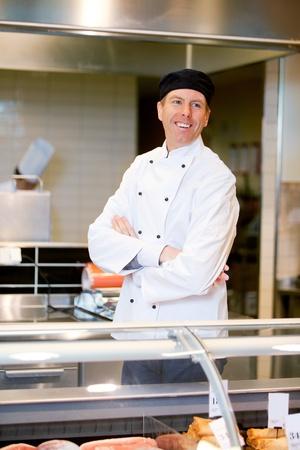 carniceria: Un carnicero sonriente feliz ayudar a un cliente en un mostrador de carne fresca Foto de archivo