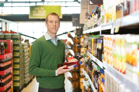 Portrait of a man comparing two products in a grocery store photo