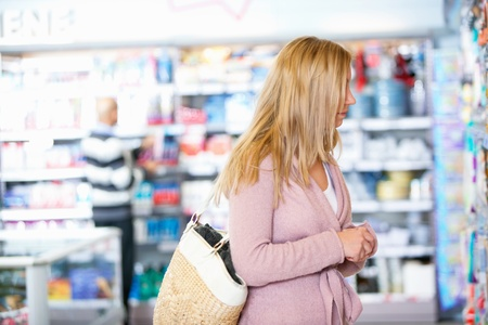 Young woman looking at goods in the supermarket with people in the background Stock Photo - 9599979