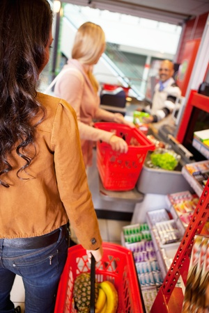 supermarket checkout: Customers carrying basket while shopping in supermarket Stock Photo