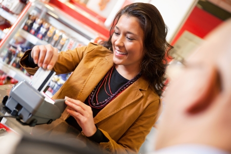 Shop assistant smiling while swiping credit card in supermarket with customer in the foreground photo