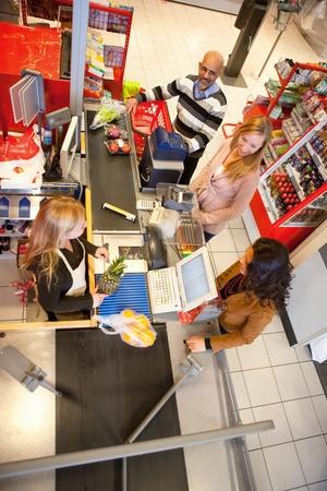 oficinista: Gran �ngulo visi�n de asistente de tienda con clientes en supermercados