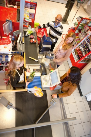 checkout: High angle view of shop assistant with customer in supermarket