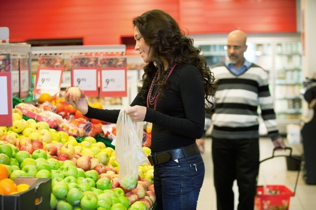 Young woman buying fruits in the supermarket with man in the background Stock Photo - 9600088