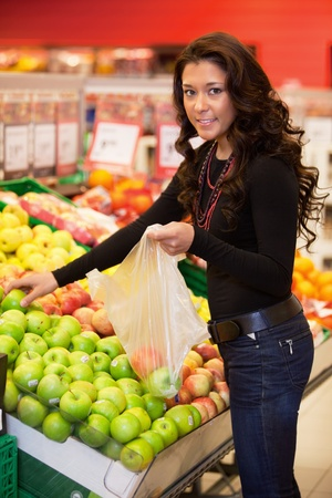 Young woman smiling while buying fruits in the supermarket photo