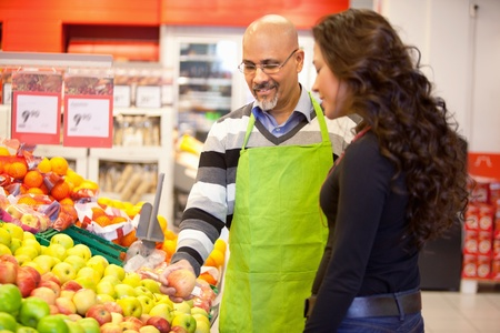 A woman buying groceries receiving help from a store clerk Stock Photo - 9599956