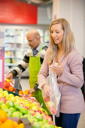 Young woman buying fruits with shop assistant in the background photo