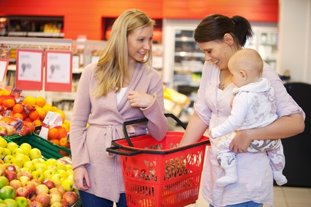 Mother carrying child with friend while shopping in supermarket photo