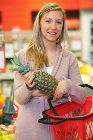 Cheerful young woman holding pineapple with basket in the supermarket photo