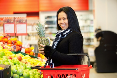 portraiture: Portrait of a cheerful young woman buying fruits in the supermarket