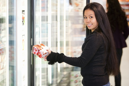 Portrait of a young woman holding box in front of refrigerator in the supermarket photo