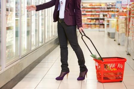 nevera: Secci�n baja de mujer de refrigerador llevando cesta en el supermercado Foto de archivo