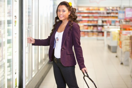 Portrait of a young woman opening refrigerator in the supermarket photo