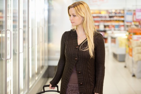 Young woman looking at goods in refrigerator section of supermarket photo