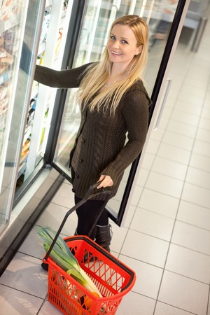 Smiling woman in a supermarket standing in front of the cooler looking at camera photo
