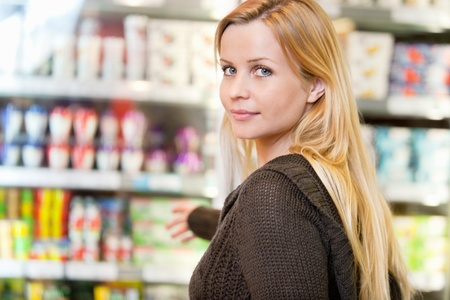 Close-up of woman reaching for products arranged in refrigerator and looking at camera Stock Photo - 9599903