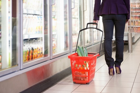 superstore: Low section of woman walking with basket near refrigerator in shopping centre Stock Photo