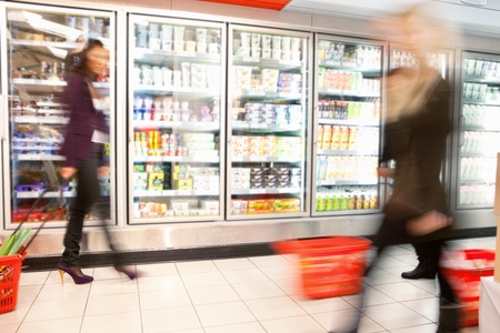 Blurred motion of people walking near refrigerator in shopping centre with baskets Stock Photo - 9600080