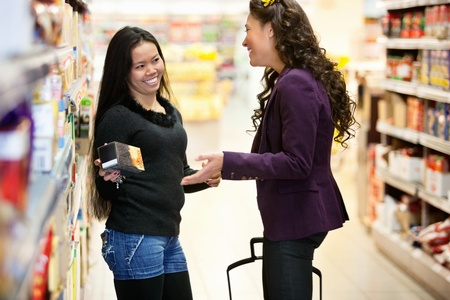 Cheerful women having conversation in shopping centre while holding product photo