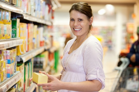 Mid adult woman holding product and looking at camera in shopping centre photo