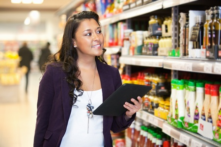 Smiling woman looking at the products while holding digital tablet with people in the background Stock Photo - 9599906