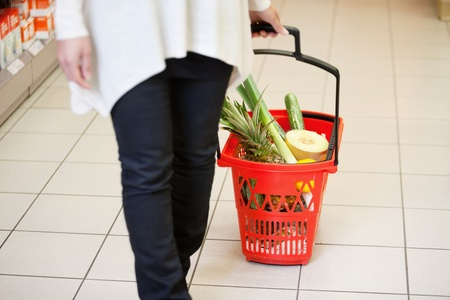 Woman holding handle of red basket in shopping store Stock Photo - 9600049