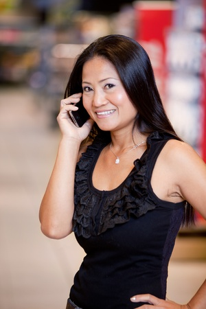 An asian woman talking on a mobile phone in a grocery store Stock Photo - 9599934