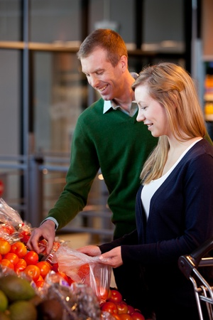 A happy couple buying fruit in a supermarket - shallow depth of field with sharp focus on woman photo