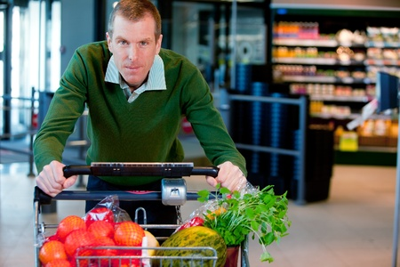 trolley: Portrait of a man pushing a grocery cart in a supermarket