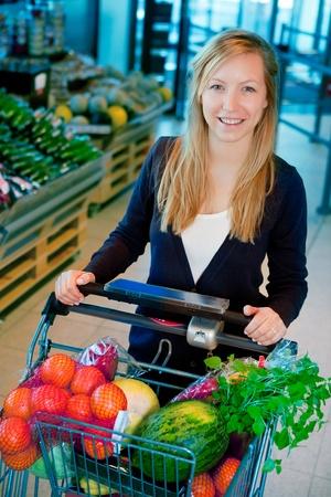 woman shopping cart: A portrait of a happy female shopper in a supermarket