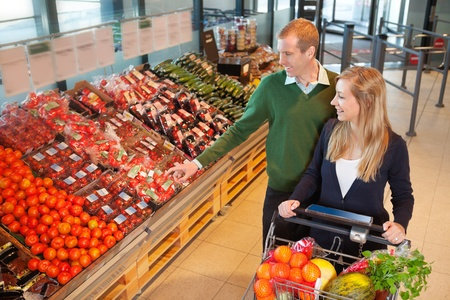 Smiling mid adult man pointing at vegetables while shopping with wife in grocery store photo