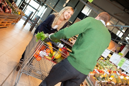 Man and woman in playful mood pushing shopping cart in shopping store photo