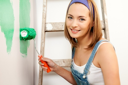 A woman with a roller brush, paiting the wall doing home improvements photo