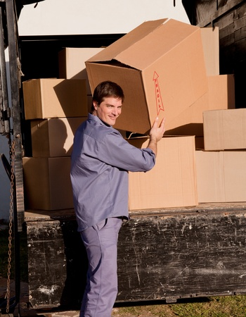 A portrait of a professional mover carrying cardboard boxes photo