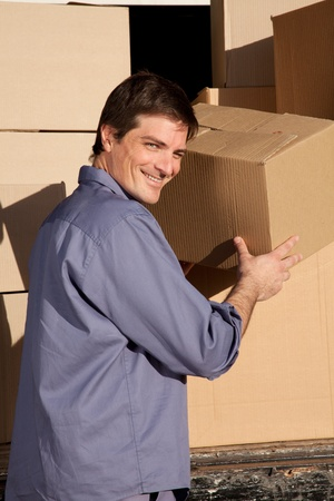 A portrait of a happy mover, moving cardboard boxes photo