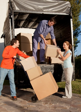 A group of people moving boxes from a trailer photo