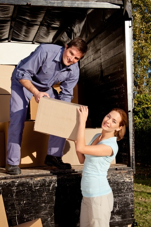 A happy couple moving boxes from a moving truck photo