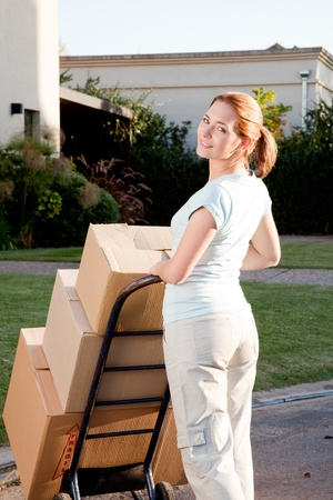 trolly: A woman moving with a stack of cardboard boxes on a trolly