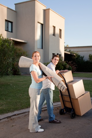 Portrait of a happy couple with moving boxes and small rug Stock Photo - 9600168