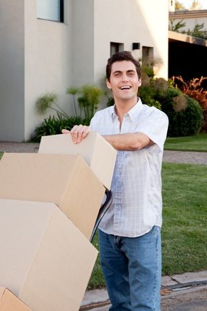 moving crate: A happy male looking at the camera pushing a dolly with moving boxes