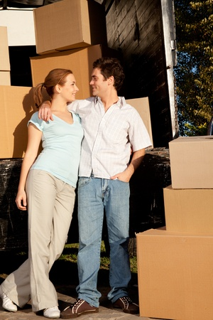 moving van: A happy couple in front of a moving van filled with cardboard boxes