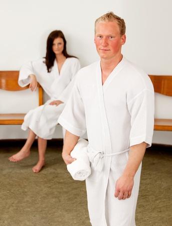 copule: A serious looking caucasian man in a bathrobe at a spa