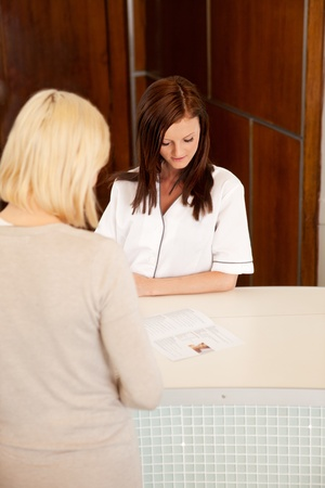 A woman in a spa reception looking at a brochure photo