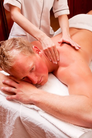 A man receiving a shoulder massage at a spa photo