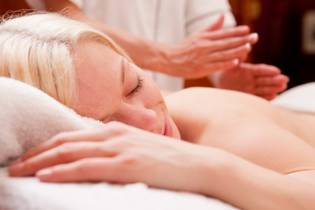 A relaxed blond woman receiving a percussive massage in a spa photo