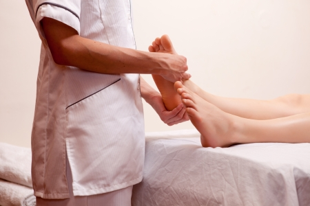 masseur: A professional masseur giving a foot massage in a spa Stock Photo