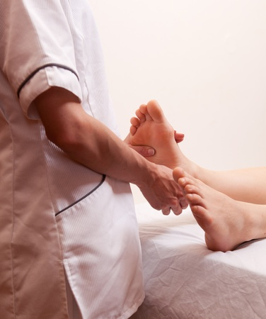 A female masseur giving a foot massage in a dayspa photo