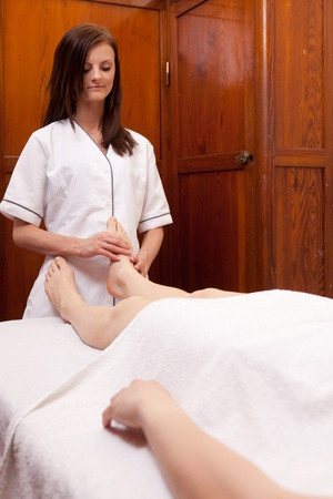 A professional masseur giving a foot massage in an old style spa photo